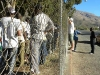 "PASSOP, an NGO supporting Zimbabweans in De Doorns, is banned from entering the IDP camp, and here holds a meeting with them through the fence! They deliver ""the Zimbabwean"" newspaper – news from home read avidly. [30 May 2010]"